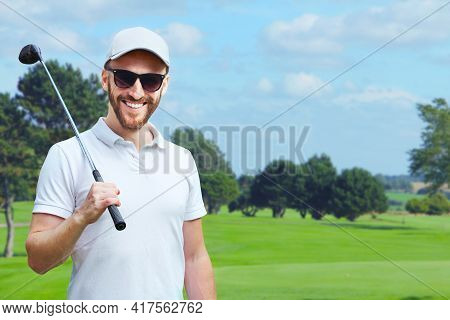 Portrait Of Male Golfer With Golf Club At Course