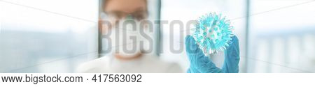 Coronavirus vaccine research lab woman researching looking at model of corona virus panoramic banner. In search of a cure research doctor holding blue sphere of COVID-19. Panoramic banner.