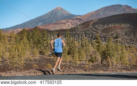 Runner athlete running on mountain road in nature landscape. View from behind of man training cardio outdoor jogging in summer forest.