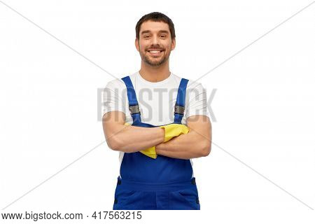 profession, cleaning service and building concept - happy smiling male worker or cleaner in overall and gloves over white background