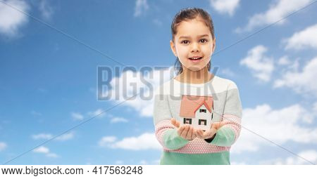 mortgage, real estate and accommodation concept - smiling girl holding house model over blue sky and clouds background
