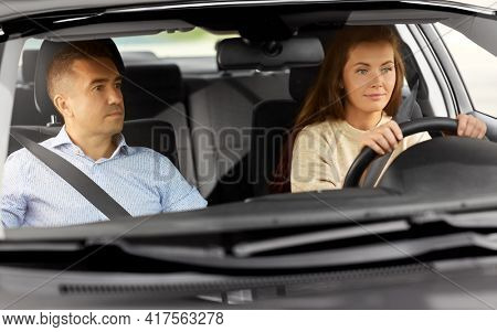 driver courses and people concept - car driving school instructor teaching young woman to drive