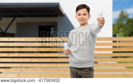 eco living and sustainability concept - smiling boy comparing energy saving light bulb with incandescent lamp over house background