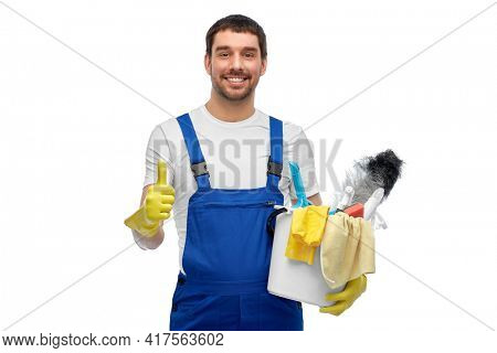 profession, service and people concept - happy smiling male worker or cleaner in overall and gloves with cleaning supplies showing thumbs up over white background
