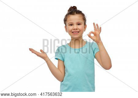 childhood, fashion and people concept - happy smiling girl holding something imaginary over white background