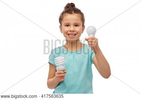 eco living and sustainability concept - smiling girl comparing energy saving light bulb with incandescent lamp over white background