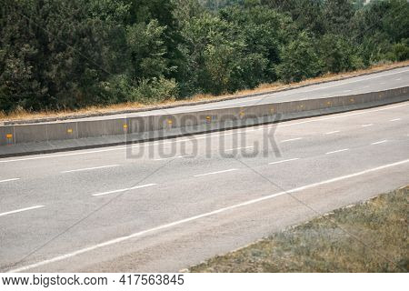an empty highway on a bright sunny day, asphalt and dividing lanes on an empty road, green trees on the side of the road, a bright summer landscape