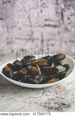 Fresh and raw sea mussels in white ceramic bowl on stone background