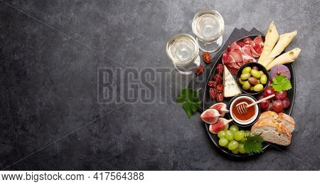 Antipasto plate with prosciutto, cheese, figs and grapes. Appetizer board. Top view flat lay with copy space