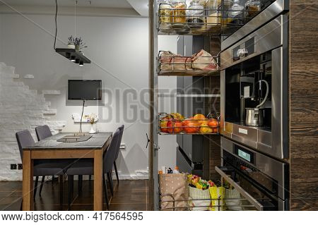 Modern large luxurious dark brown kitchen showcase interior, with dining table showing big vertical drawer with storage compartment pulled out