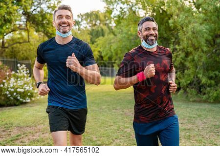 Happy mature man with indian friend running at park with surgical face mask during covid-19 pandemic. Active mid adult man jogging outdoor with lowered face mask against coronavirus.