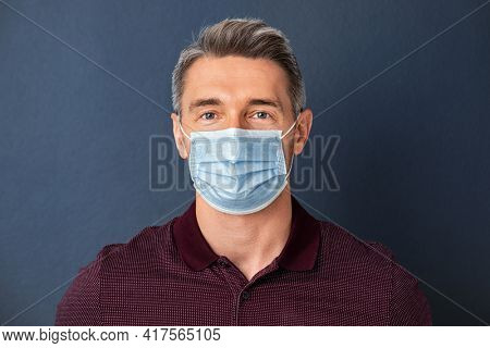 Handsome mature man wearing face mask isolated against grey wall. Smiling positive man wearing surgical mask and looking at camera isolated on gray background. Portrait of mid adult guy despite covid.