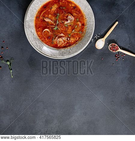 Russian cuisine - Solyanka Soup on dark textured table. Spicy and sour soup with meat slice and vegetables. Ceramic bowl on dark background. Top view