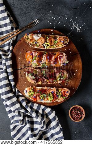 Italian Bruschetta antipasto - Grilled Bread topped with tomato, vegetables, cured meat, salted fish. Various bruschetta on dark textured table top view. Food flat lay, italian rustic dish concept