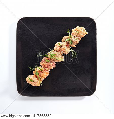 Gunkan Sushi - Gunkan Maki Sushi with Seafood and Spicy Sauce. Sushi with Rice inside and wrapped nori seaweed. Delicious Gunkan Sushi on black slate plate. Isolated on white background. Top view
