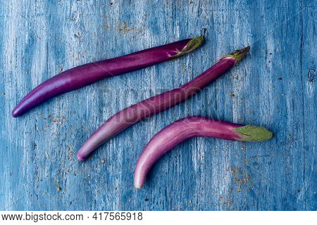 high angle view of some purple japanese eggplants, with its peculiar long shape, on a rustic blue wooden table