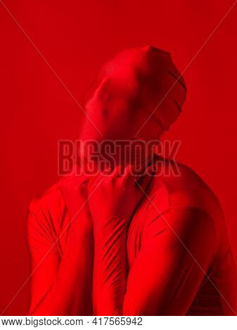 Crazy Red Man On A Red Background. Figure In A Leotard Covering The Whole Body