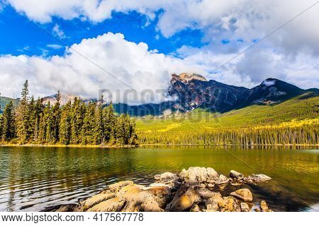 Pyramid Lake. The lake is covered with light water ripples. Cold sunny day in the Rocky Mountains of Canada. Mount Pyramid is covered by cumulus clouds.