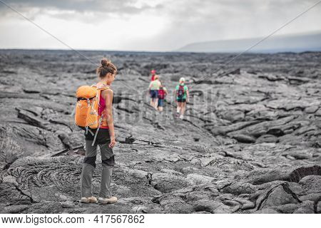 Hiking group of hikers walking on Hawaii volcano lava field hike adventure happy woman with backpack in Big Island, Hawaii. Tourists walking on guided tour trail outdoor USA summer travel vacation.