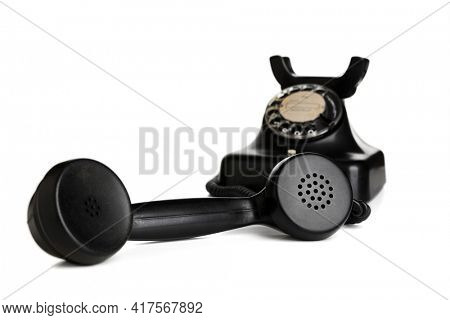 Vintage black telephone with receiver taken off the hook isolated on white background, selective focus