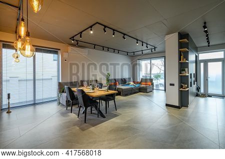 Modern luxurious studio apartment interior with dining table in large living room