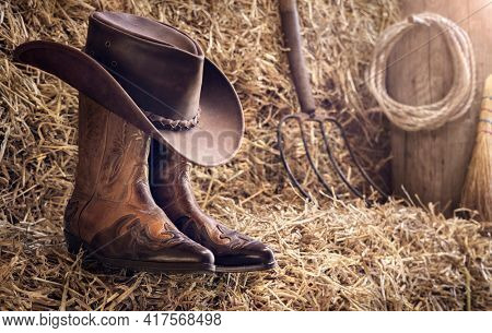 Country music festival live concert or rodeo with cowboy hat and boots in barn background