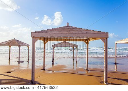 Winter in Israel. Windy sunny day on the Mediterranean coast. Beach canopies on the sand are illuminated by sunset. Powerful winter surf takes off with snow-white foam