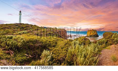 Vivid and dramatic sunset over panorama of a famous Split Point Lighthouse and Eagle Rock in the sea. Aireys Inlet at Great Ocean Road on southern coast of Victoria state, Australia.