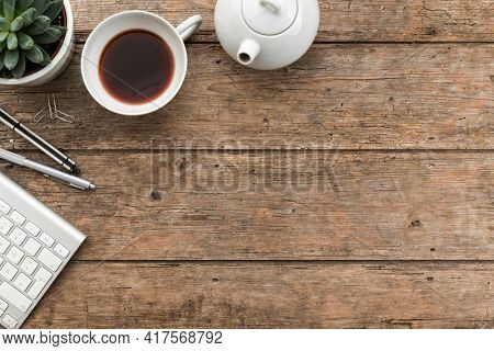 Wooden hipster desk with computer keyboard, tea pot and cup, potted succulent plant and pencil. Top view with copy space , flat lay.