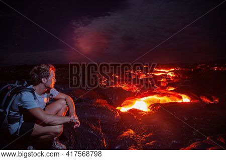 Lava flow man hiker on night hike watching magma erupting flowing from volcanic eruption in Kilauea volcano, Big Island, Hawaii travel. Long exposure.
