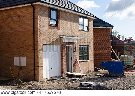 An Ordinary New Semi-detached House For Sale And Two Recycling Skips In Front Of It