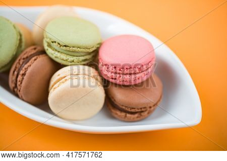 Sweet Delicous Macarons In A Bowl With Orange Background