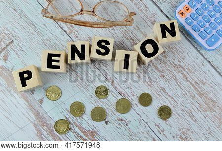 Top View Of Coins, Eyeglasses, Calculator And Wooden Blocks Written With Pension.