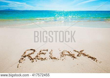 Realax word writing on tropical sea beach