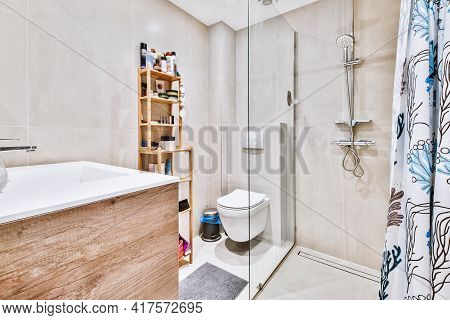 Flush Toilet And Shower Cabin With Glass Partition And Curtain Located Near Sink And Shelf With Cosm