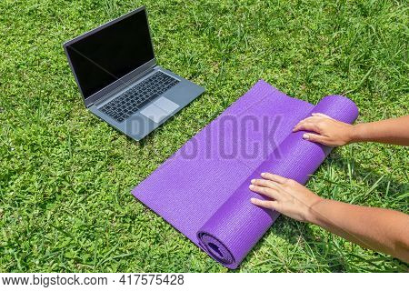 Female Hands Spread The Yoga Mat On The Green Grass. Online Sports Training In The Garden