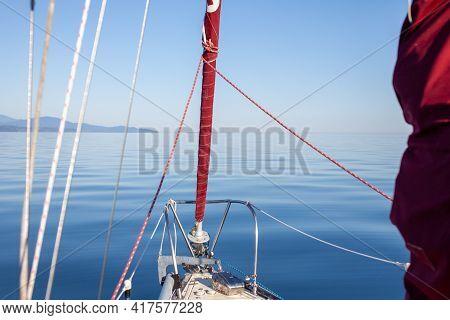 A Sailboat Motors Along The Coastline Of British-columbia's Sunshine Coast, Along The Pacific Northw