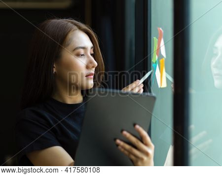 Female Office Worker Working With Sticky Note With Idea On Glass Wall And Digital Tablet