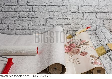 Rolled Rolls Of Wallpaper, A Brush And A Roller Are Prepared For Apartment Renovation. Home Renovati