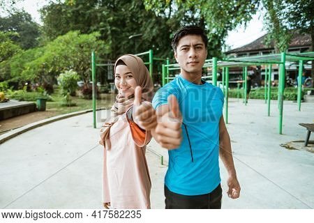 A Young Man And A Girl In A Veil Smile While Standing Back To Back With Thumbs Up