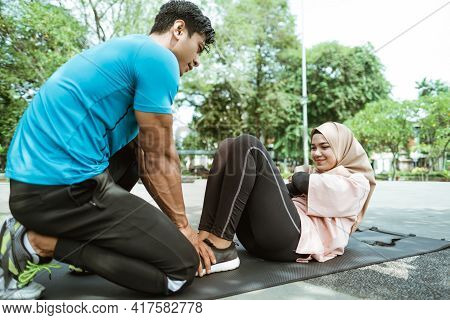 A Young Man Helps Hold The Legs Of A Veiled Girl Doing Sit Ups While Exercising Outdoors