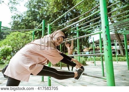 Smiling Girl In A Veil Does Leg Stretches Over An Iron Bar