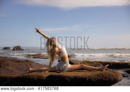 Yoga Practice. Slim Caucasian Woman Practicing Hanumanasana, Monkey Pose Or Front Split. One Arm Ras