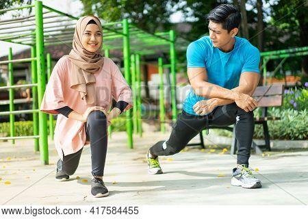A Man And A Girl In A Veil In Gym Clothes Doing Lunges Movements