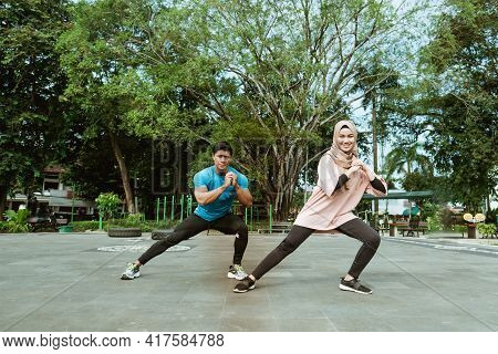 A Young Man And A Veiled Girl In Gym Clothes Doing The Leg Warm-up Movement Together Before Exercisi