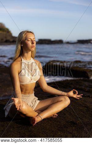 Attractive Woman Practicing Yoga On The Beach. Sitting In Padmasana, Lotus Pose. Hands In Gyan Mudra