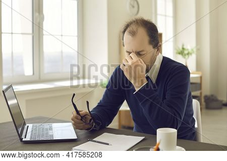 Mature Man Holding Glasses Massaging Nose Feel Eye Strain After Work On Laptop