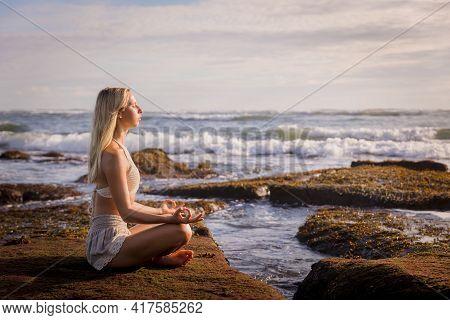 Woman Practicing Yoga On The Beach. Sitting In Padmasana, Lotus Pose. Hands In Gyan Mudra. Positive