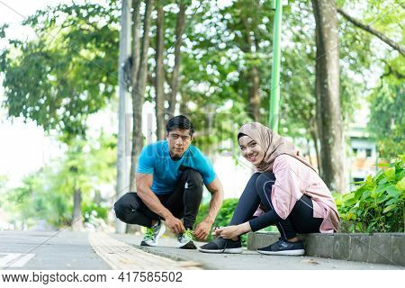 A Veiled Girl And A Man Squat As They Prepare To Fix Their Shoelaces Before Jogging