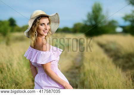 Young Freckled Woman In A Straw Hat Posing In Nature. Portrait Of A Smiling Caucasian Girl Walking I